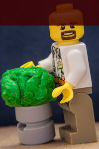 """Lego man standing next to """"the world's largest ball of phlegm."""" Actually, a glob of gum. Part of the lego man's head is missing, due to cropping the photo to a different aspect ratio."""