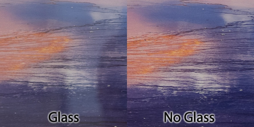 Comparison of an inset of an image of Grand Prismatic Spring. The left side is protect by glass but has contrast-cutting glare. The right side is protected only by an archival spray, not glass. Colors and contrast appear better without the reflection on the print.