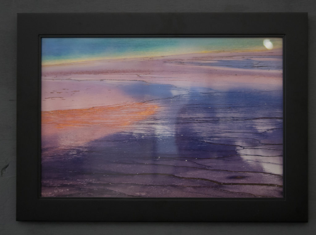 Print of Grand Prismatic Spring behind glass. Reflections and glare from poor lighting hinder the view of the print.