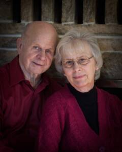 Portrait of my parents, dressed in dark maroon in front of a stone fireplace.
