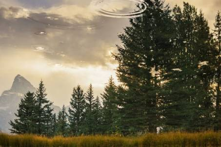 Golden twilight sky, Grand Tetons, and tall trees in a crystal clear reflection in the Snake River. Ripples in the sky spiral away from the viewer.